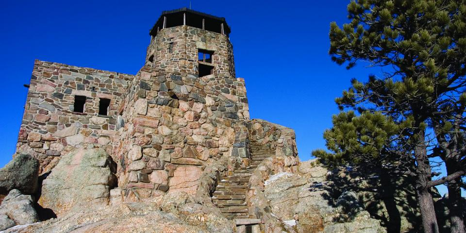 A stone lookout tower rises from the very top of Harney Peak.